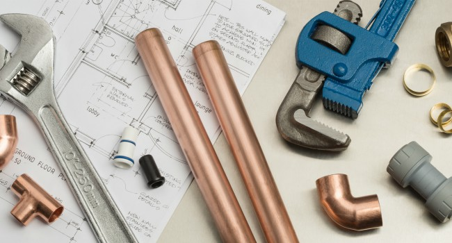 Various plumbers tools and plumbing materials including copper pipe, elbow joint, wrench and spanner. shot on top of architects house plans on a bright stainless steel background.